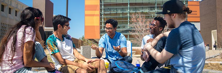 Four students talking outside near Davis Hall on UB's North Campus.